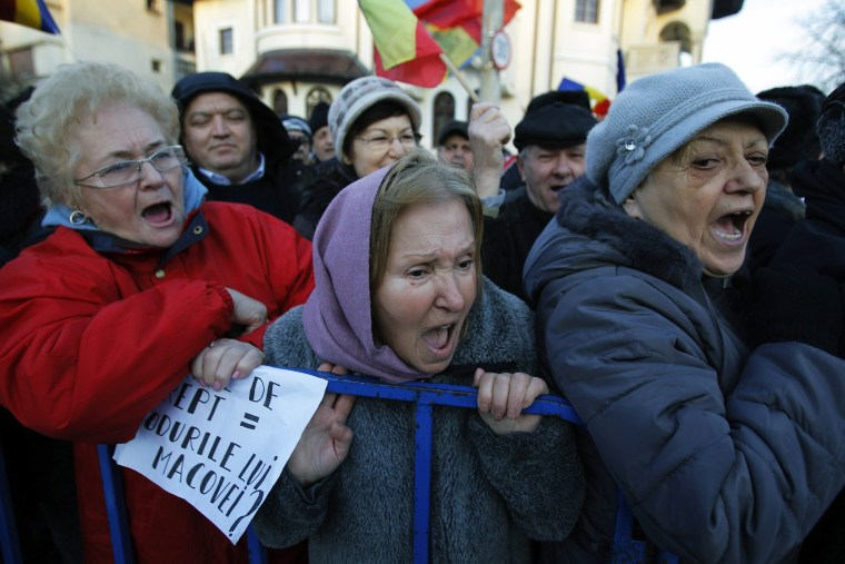 Image: People shout pro-government slogans during a rally in front of the Cotroceni presidential palace in Bucharest.
