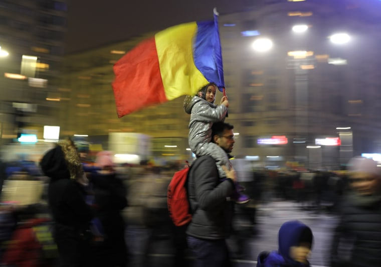 Image: A young child carries the Romanian national flag.