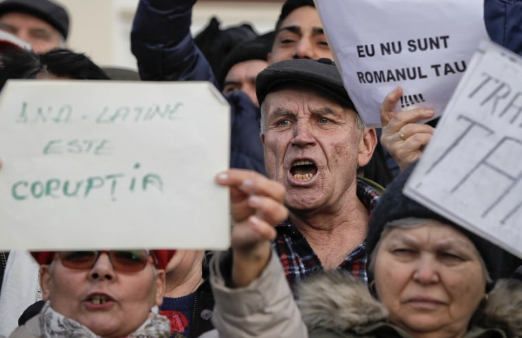 "Image: People hold banners that read ""I am not your Romanian"" while shouting slogans against Romanian President Klaus Iohannis during a pro-government demonstration joined by hundreds in Bucharest."