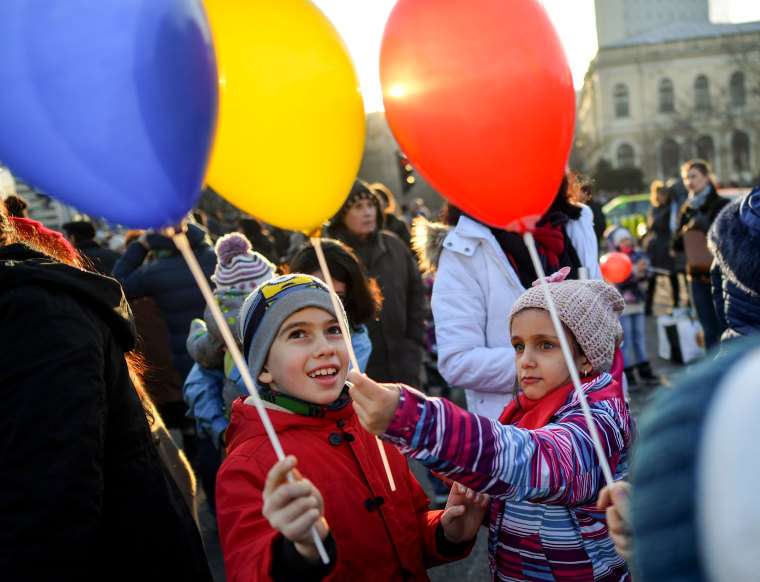 Image: Children hold balloons in the colors of the Romanian flag.