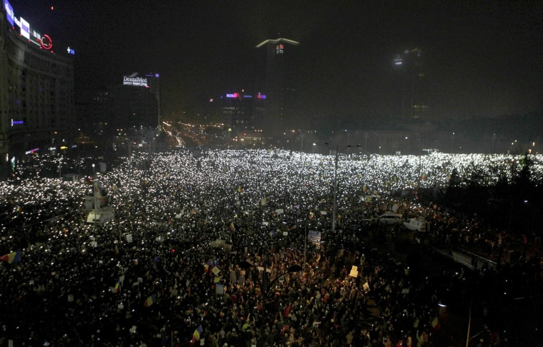 Image: Protesters use phones and flashlights during a protest in Victoriei Square, in Bucharest.