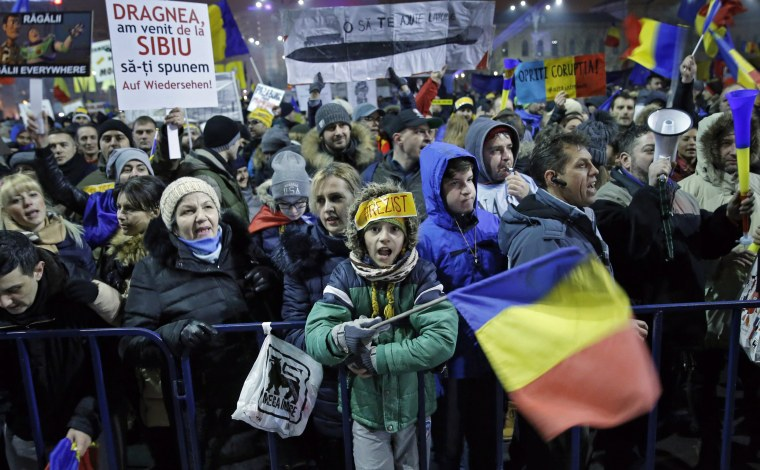 Image: People shout slogans and wave placards while attending  a protest in front of government headquarters in Bucharest.