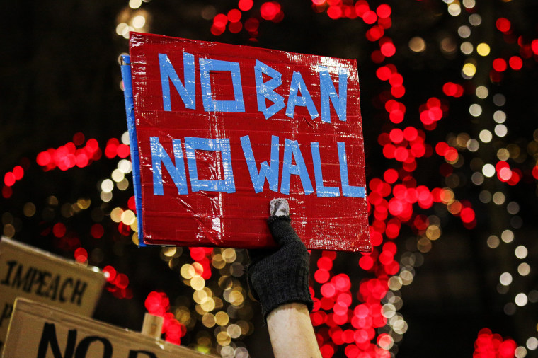 Image: A man holds a sign during a protest held in response to President Trump's travel ban in Seattle, Washington on Jan. 29.