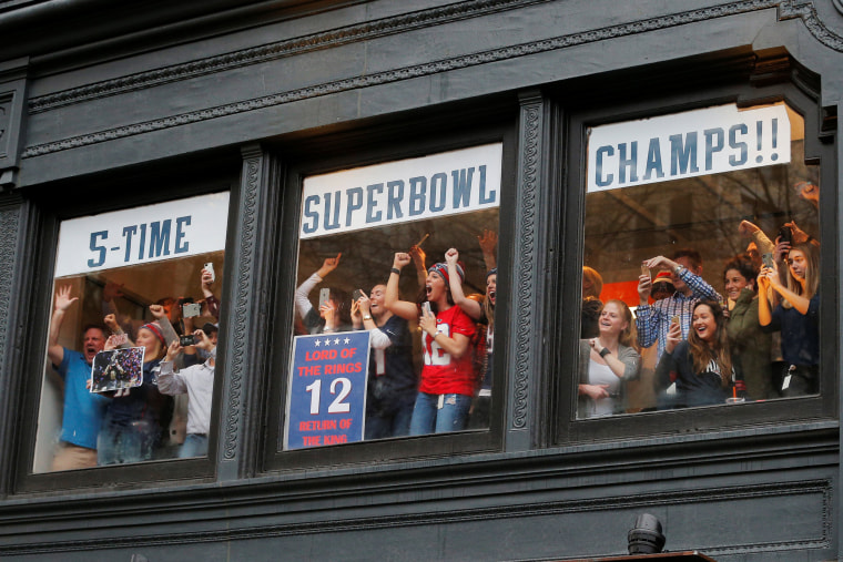 Image: Fans in office windows watch the New England Patriots victory parade through the streets of Boston after winning Super Bowl LI, in Boston