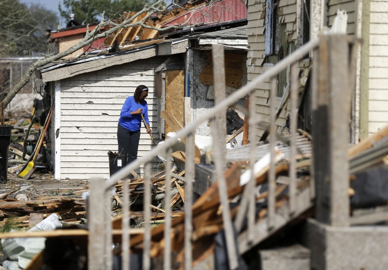 Image: A woman clears debris from her damaged home in the aftermath of the tornado that tore through the New Orleans East on Feb. 8.