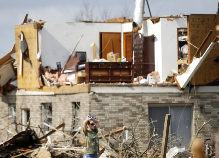 Image: A woman walks past a destroyed home in the aftermath of the tornado that tore through the New Orleans East section of New Orleans on Feb. 8.