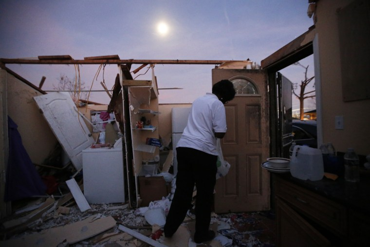 Image: With the moon rising overhead, Theresa Perkins retrieves some belongings from inside of the destroyed home of her friend Thelma Packnett, in the aftermath of the tornado that tore through the New Orleans East section of New Orleans on Feb. 8.