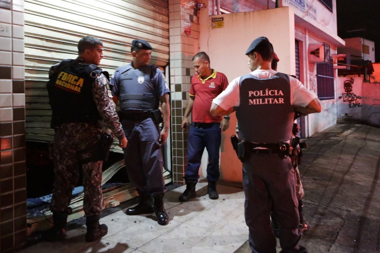 Military police check the broken entrance of a store that was looted in Vitoria, Espirito Santo state, Brazil, Wednesday, Feb 8, 2017.