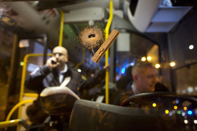 Image: A bullet hole is seen on the windshield of a bus at the scene of a shooting attack in Petah Tikva