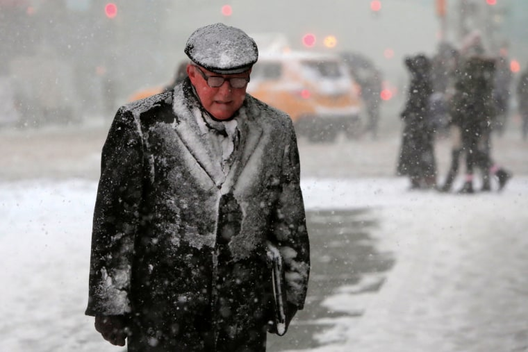 Image: A man walks in Times Square as snow falls in Manhattan