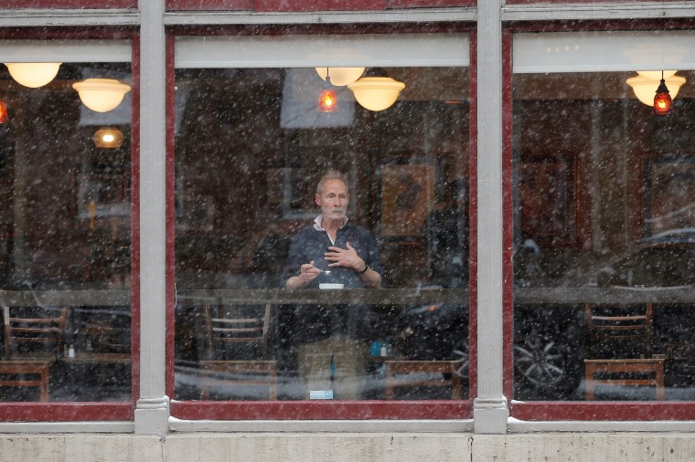Image: A man looks out from a cafe's window during a winter nor'easter snow storm in Boston