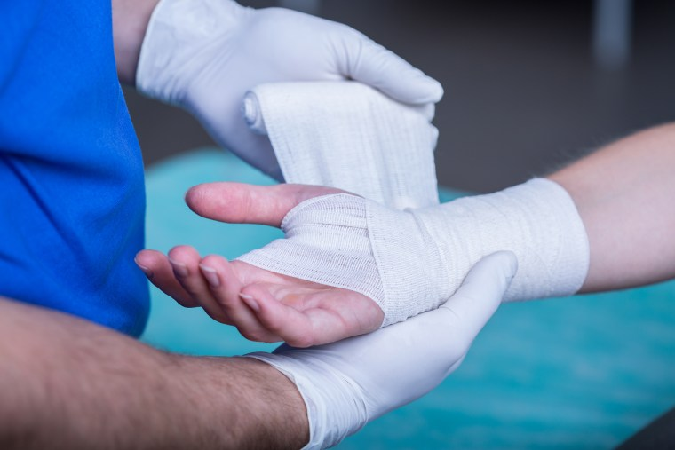 Image: A doctor bandages a hand injury.