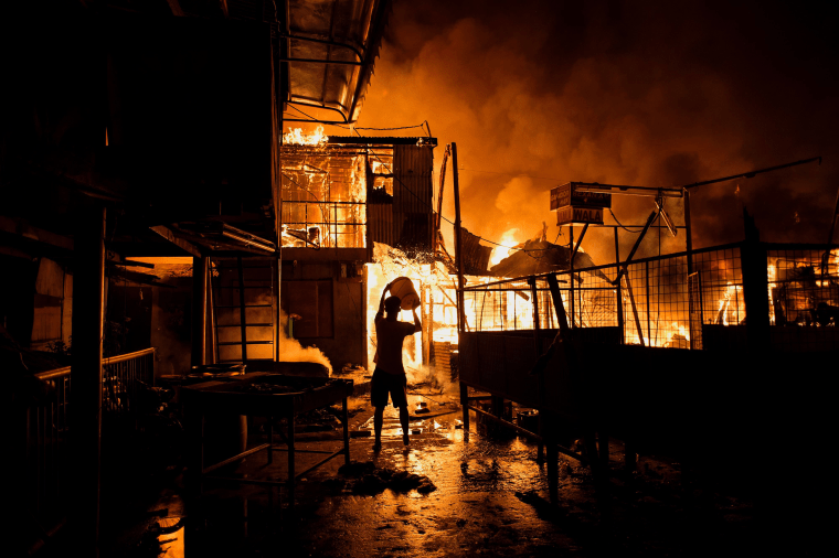 Image: A resident pours water on a fire as it destroys hundreds of houses at an informal settlers community in Manila