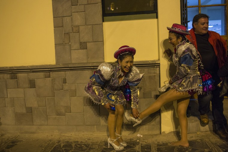 Image: Dancers laugh as they remove their shoes after performing in the Virgin of Candelaria celebrations