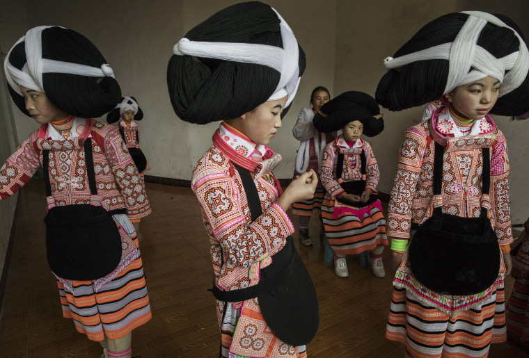 Image: Teenage girls of the Long Horn Miao ethnic minority group wear headdresses as they prepare to celebrate Tiaohua