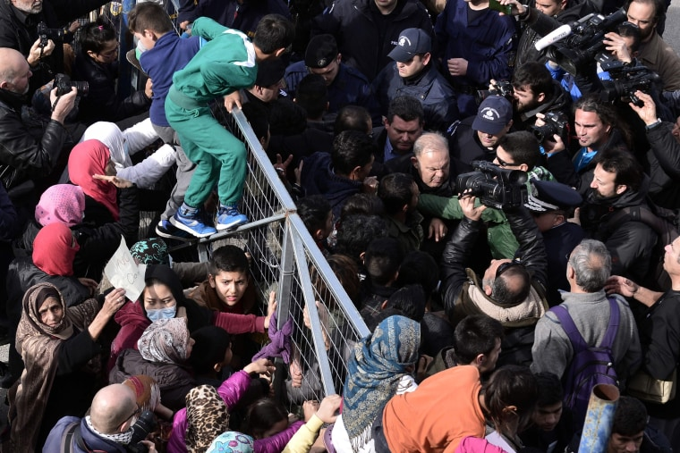 Image: Migrants block the entrance of the Hellinikon camp in Athens in protest at poor living conditions