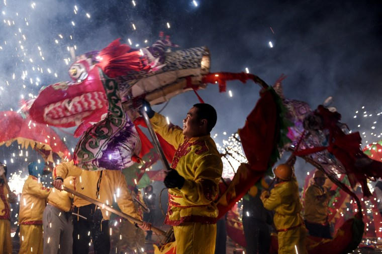 Image: People perform dragon dances with fireworks during a local celebration ahead of China's Lantern Festival in Zunyi