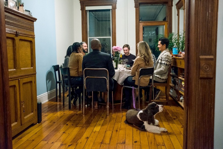 Image: A group of strangers gather for dinner as a part of the #100Days100Dinners initiative that unites people from opposing ideologies for an evening of food drinks and relationship building.