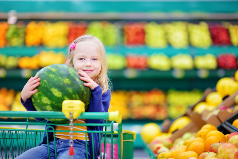 Little girl holding watermelon in shopping cart