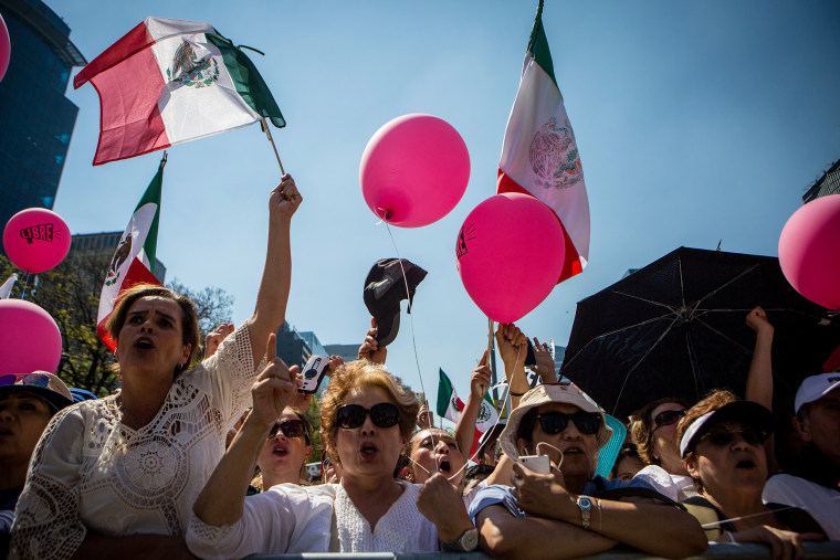 Image: People shout slogans during a protest against Donald Trump's anti-immigrant politics and the wall between the Mexico - U.S. border in Mexico City, Feb. 12, 2017. Around 20,000 people attended the protest.