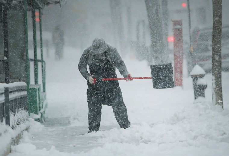 Image: A man shovels snow during a storm in New York