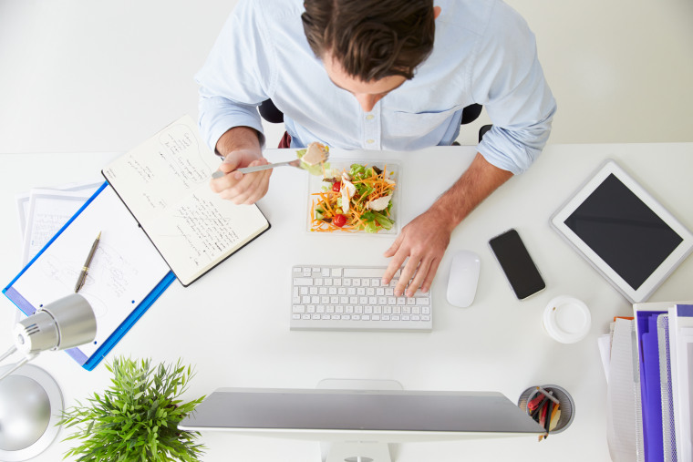 Image: A man eats lunch at his desk