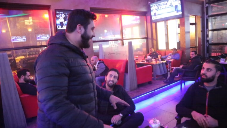 Image: Moe Qasim jumps into a conversation at the Signature Cafe hookah lounge