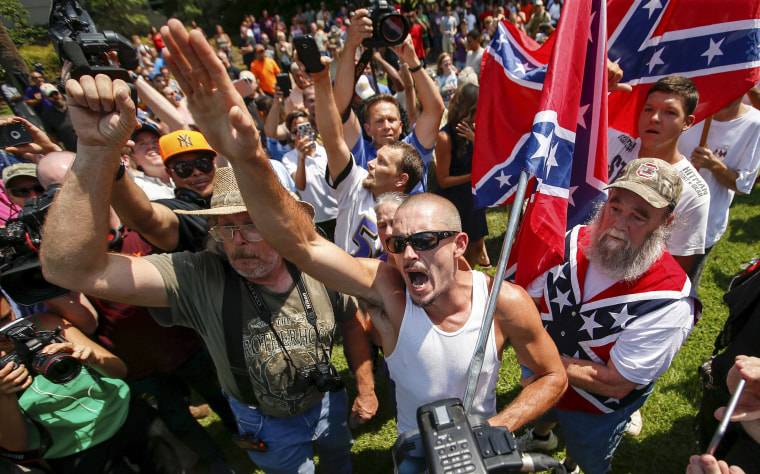 Image: A supporter for the Ku Klux Klan and the Confederate flag yells at opposing demonstrators during a rally at the statehouse in Columbia