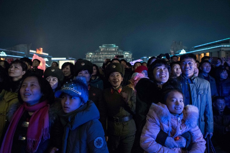 Image: People watch a fireworks display as they visit an ice festival near the Taedong river