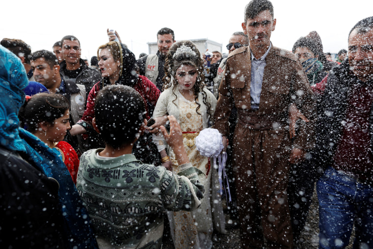 Image: Iraqi newlyweds who fled Mosul, Hussain Zeeno Zannun, 26, and Chahad, 16, are showered in foam during their wedding party at Khazer camp