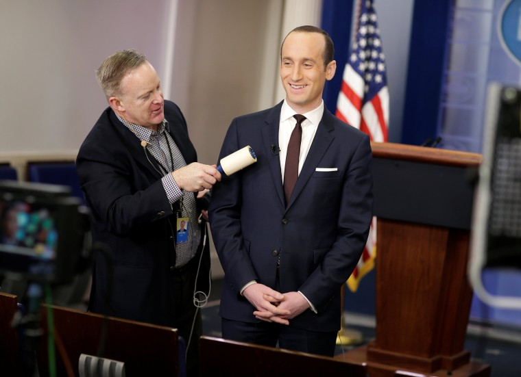 Image: White House Press Secretary Spicer removes lint from Senior White House Advisor Miller's jacket as he waits to go on the air in the White House Briefing Room in Washington.