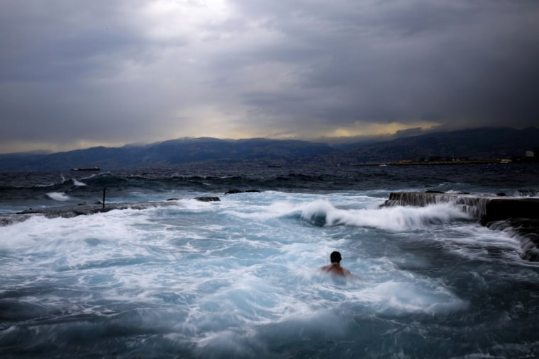 Image: A swimmer goes for an early morning dip in the Mediterranean sea
