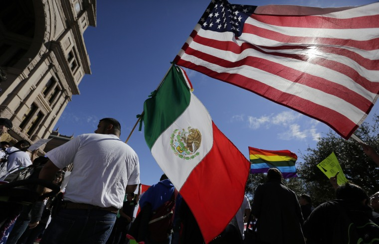 Image: A man hold the U.S and Mexico flags during a march and rally during an immigration protest