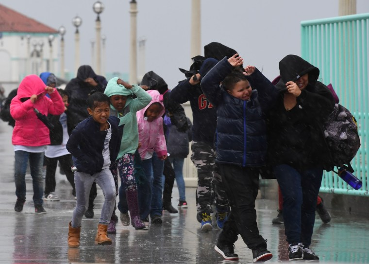 Image: Schoolchildren race back to their bus after getting caught in heavy rain during a school trip