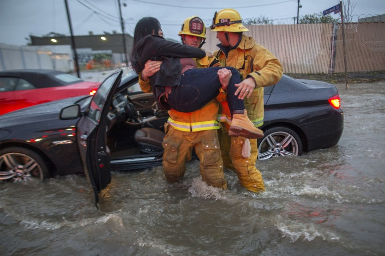 Image: A firefighter carries a woman from her car after it was caught in street flooding