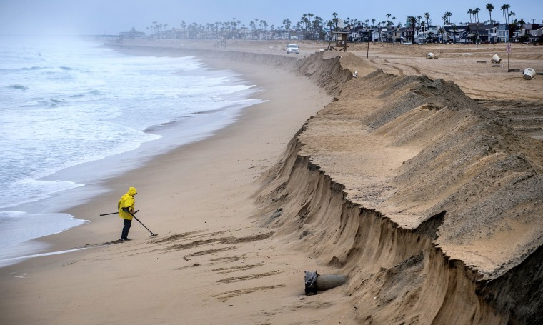 Image: Stan Ross of Newport Beach digs up some sand near the Balboa Pier in Newport Beach