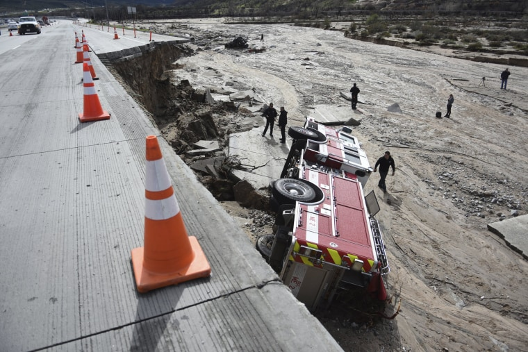 Image: Officials look over the scene where a San Bernardino County Fire Department fire engine fell from southbound Interstate 15