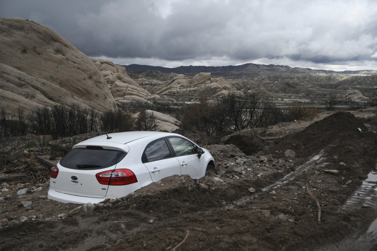 Image: An abandoned Kia sedan is seen stuck in heavy mud in Lone Pine Canyon Road