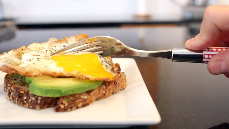 Cutting into a fried egg with a fork