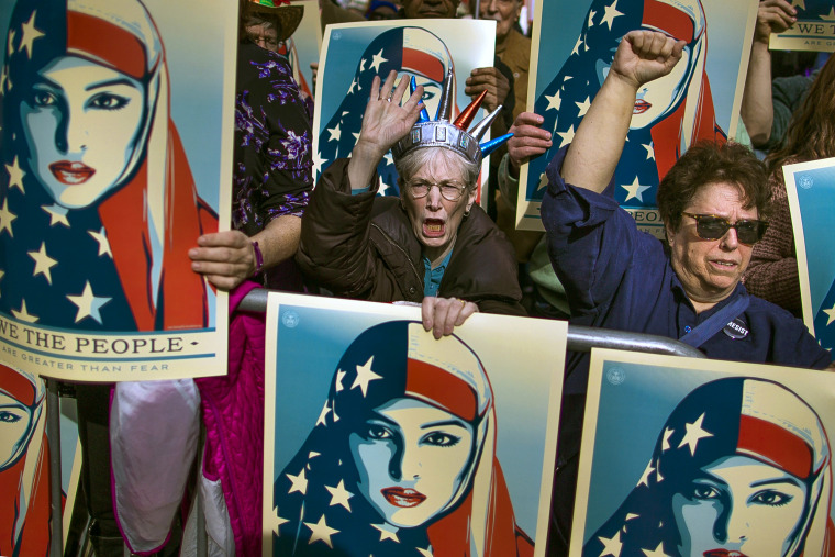 Image: People carry posters during the rally against President Trump's executive order banning travel from seven Muslim-majority nations, in Times Square, Feb. 19, 2017.