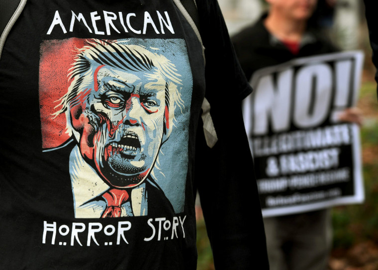 "Image: Protesters carry anti-Trump signs during a ""Not My President Day"" demonstration outside City Hall in Los Angeles, California, on Feb. 20, 2017."