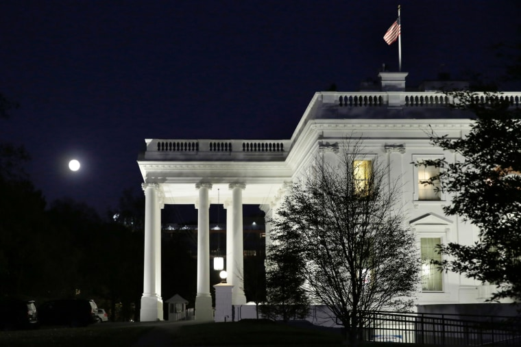 Image: The moon rises over the White House in Washington, D.C.