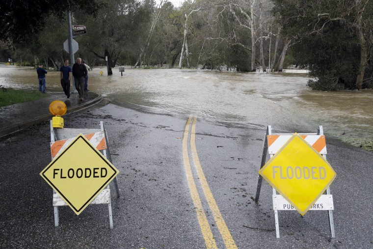 Image: Signs block a road which runs into the overflowing Coyote Creek, Feb. 21, 2017, in Morgan Hill, Calif.