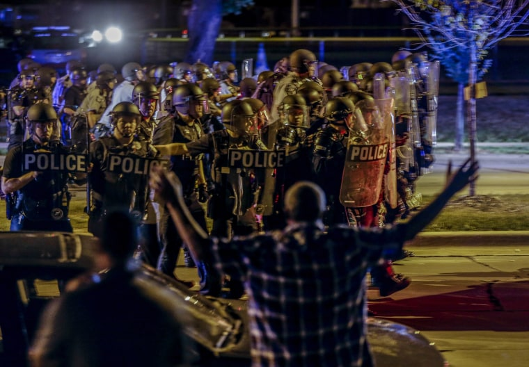 Police move in on a group of protesters throwing rocks at them in Milwaukee, Sunday, Aug. 14, 2016. The police shooting of a black man spurred two nights of violence in Milwaukee.