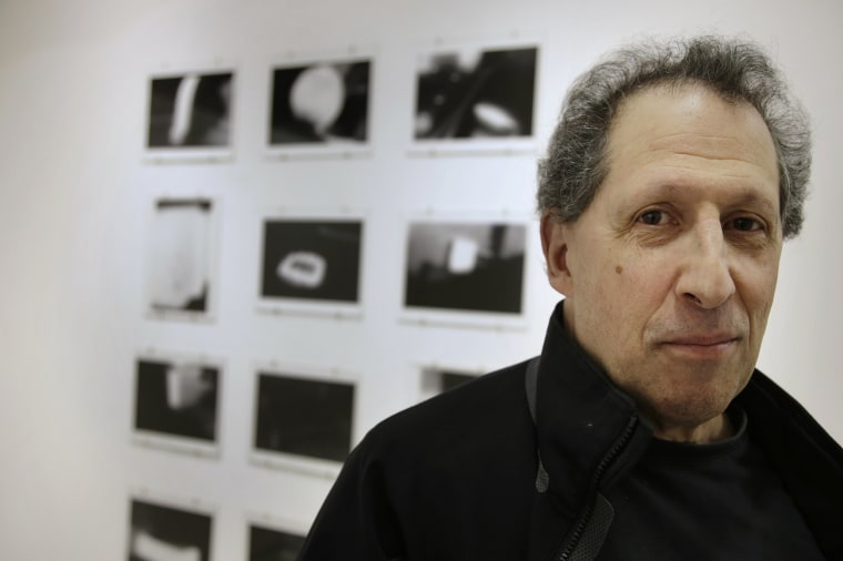 Image: Karl Baden stands in front of an exhibit of his photographs
