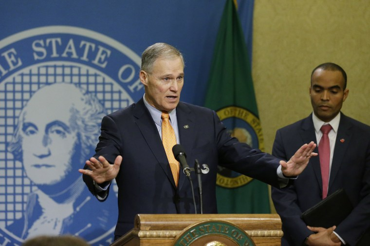 Image: Washington Gov. Jay Inslee, left, talks to reporters, as general counsel Nick Brown looks on at right, Feb. 23, 2017, at the Capitol in Olympia, Wash.