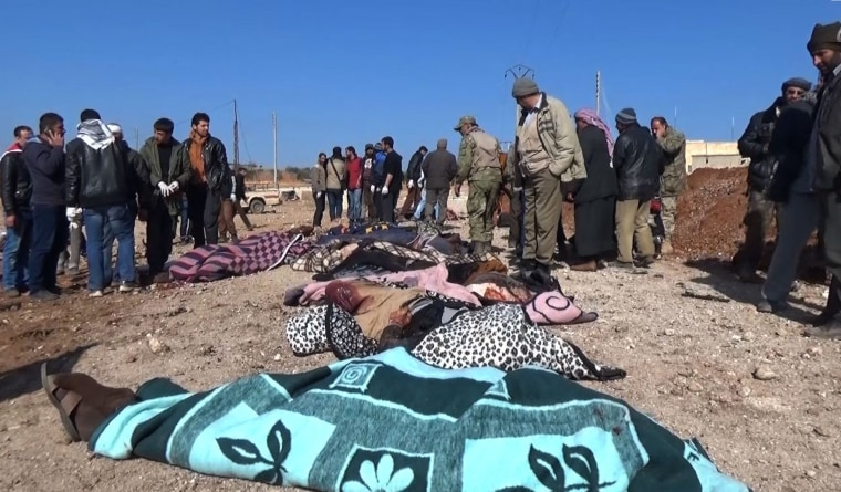 Image: Bodies wrapped in blankets lie on the ground after a bomber blew up a vehicle packed with explosives just outside the Syrian border town of al-Bab