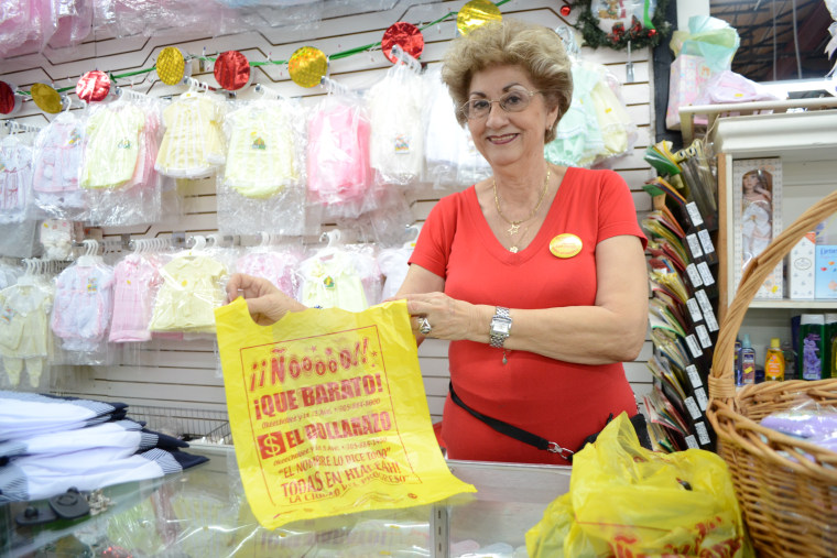 "Inside the store ""Ñoo Que Barato"" or ""Damn That's Cheap"" in Hialeah, an employee stands in front of the section where new born baby items popular among Latinos are sold."