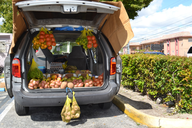 A vendor sells fruits and vegetables from the trunk of a van in the parking lot of a strip mall in Hialeah.