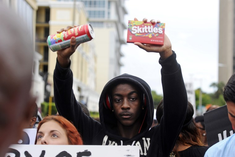 Image: Brendon Daniels holds up a can of iced tea and a bag of skittles during a rally in support of slain teenager Trayvon Martin in Orlando, Florida, July 17, 2013.